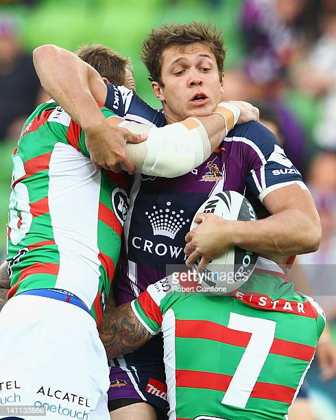 Matt Duffie of the Storm is tackled by John Sutton and Adam Reynolds of the Rabbitohs during the round two NRL match between the Melbourne Storm and...