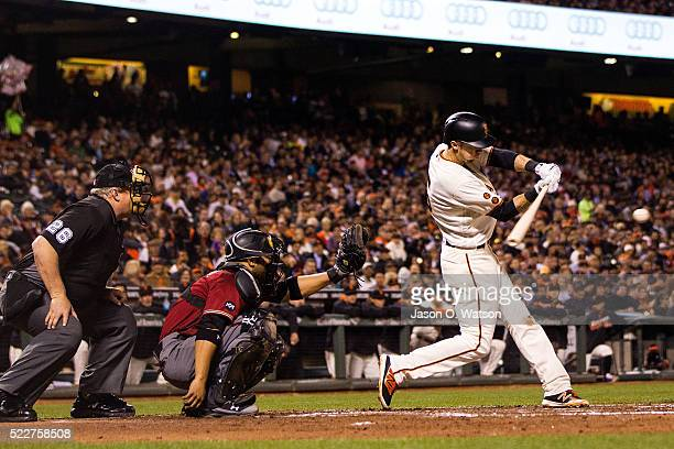 Matt Duffy of the San Francisco Giants hits a double in front of Welington Castillo of the Arizona Diamondbacks and umpire Bill Miller during the...