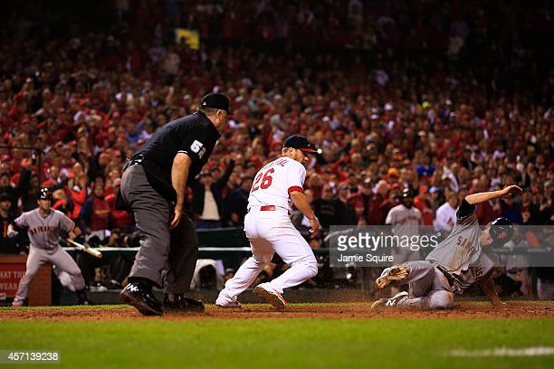 Matt Duffy of the San Francisco Giants slides into home to score on a wild pitch in the ninth inning as Trevor Rosenthal of the St Louis Cardinals...