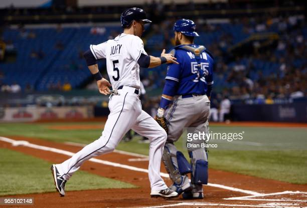 Matt Duffy of the Tampa Bay Rays crosses home plate ahead of catcher Russell Martin of the Toronto Blue Jays as he scores off of an error by second...