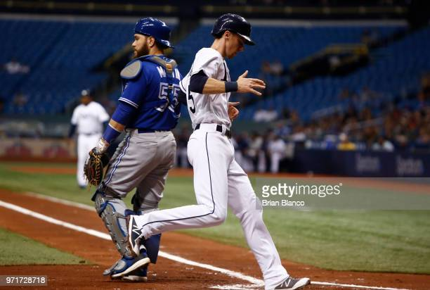 Matt Duffy of the Tampa Bay Rays crosses home plate ahead of catcher Russell Martin of the Toronto Blue Jays to score off of a sacrifice fly by Joey...