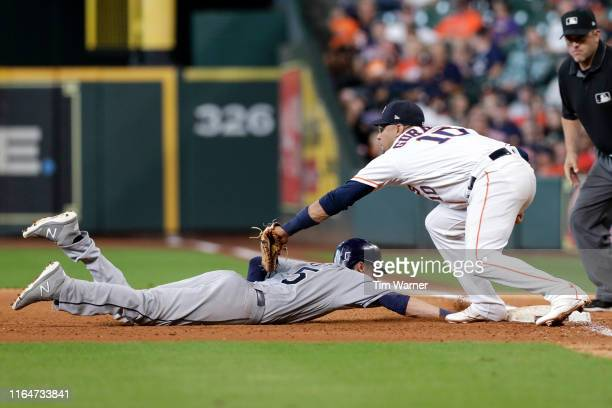 Matt Duffy of the Tampa Bay Rays dives safely to first base as Yuli Gurriel of the Houston Astros applies the tag in the seventh inning at Minute...