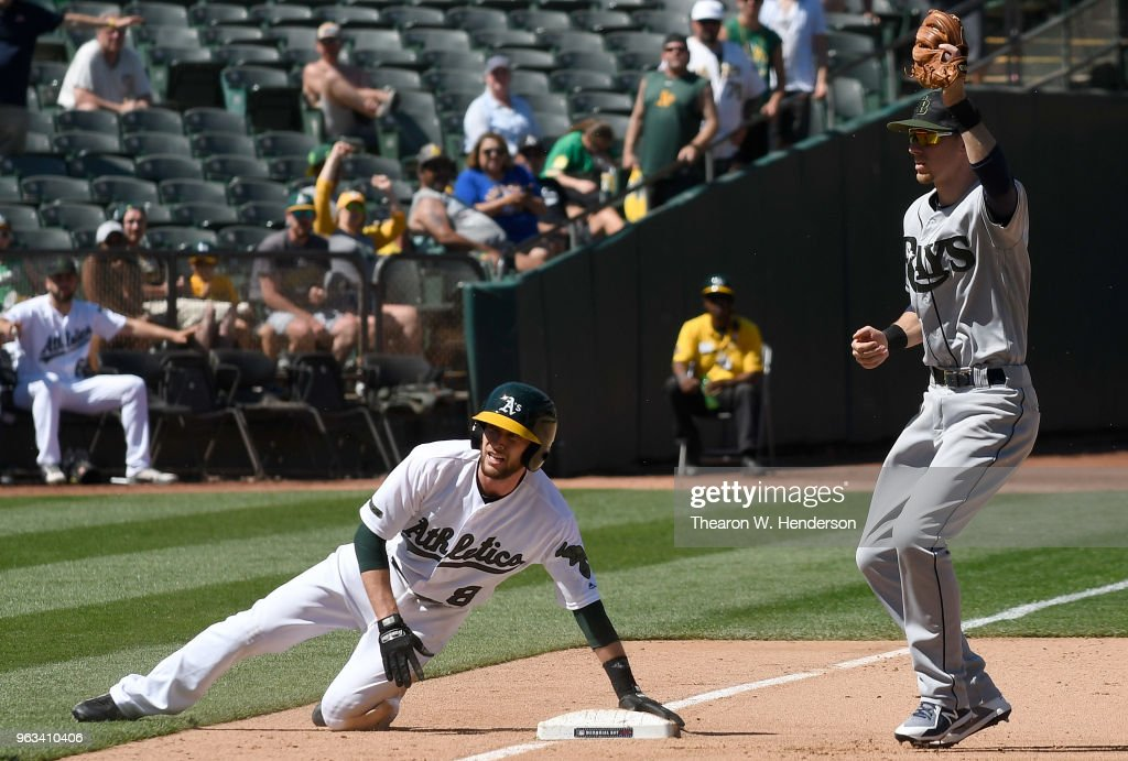 Matt Duffy #5 of the Tampa Bay Rays get the put out at third base on Jed Lowrie #8 of the Oakland Athletics in the bottom of the ninth inning at the Oakland Alameda Coliseum on May 28, 2018 in Oakland, California.