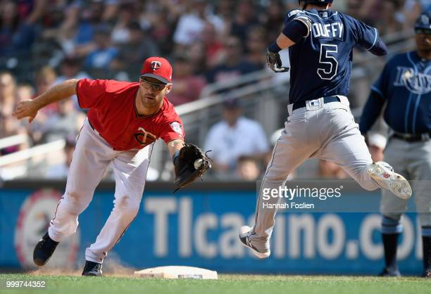 Matt Duffy of the Tampa Bay Rays reaches safely as Joe Mauer of the Minnesota Twins is pulled from first base during the eighth inning of the game on...