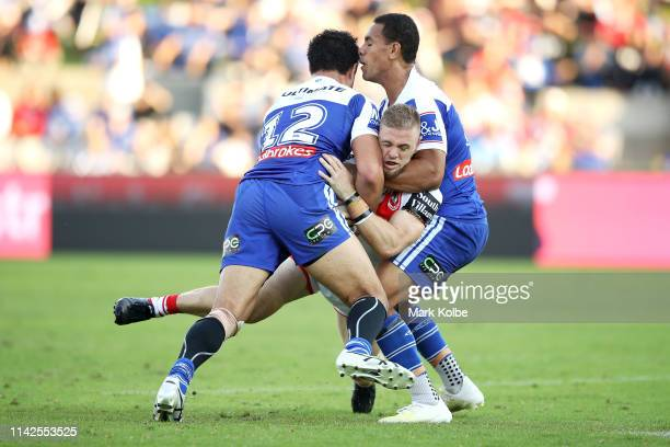 Matt Dufty of the Dragons is tackled by Corey Harawira-Naera and Will Hopoate of the Bulldogs during the round five NRL match between the St George...