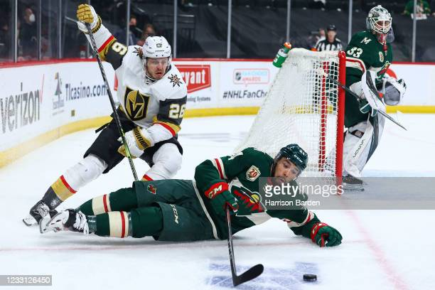 Matt Dumba of the Minnesota Wild and Mattias Janmark of the Vegas Golden Knights fight for the puck during the first period in Game Six of the First...