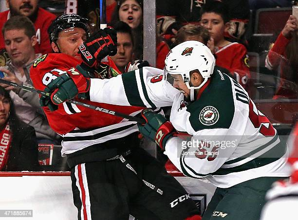 Matt Dumba of the Minnesota Wild hits Marian Hossa of the Chicago Blackhawks along the boards in Game One of the Western Conference Semifinals during...