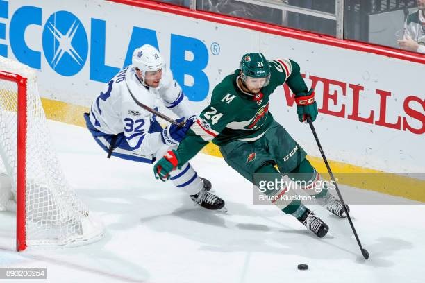 Matt Dumba of the Minnesota Wild skates with the puck while Josh Leivo of the Toronto Maple Leafs defends during the game at the Xcel Energy Center...