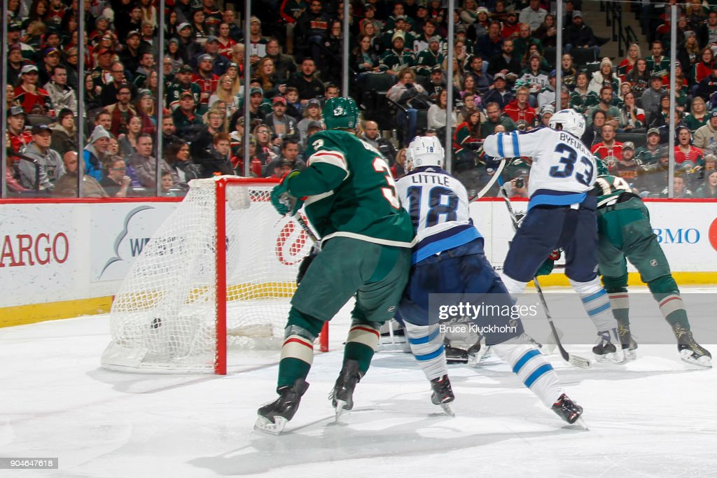 Matt Dumba #24 scores a goal as his Minnesota Wild teammates (L-R) Charlie Coyle #3 and Joel Eriksson Ek #14 battle for position with Bryan Little #18 and Dustin Byfuglien #33 of the Winnipeg Jets during the game at the Xcel Energy Center on January 13, 2018 in St. Paul, Minnesota.