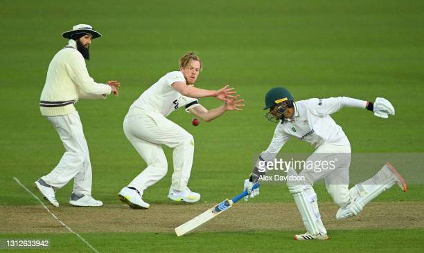 Matt Dunn of Surrey fields the ball as Hassan Azad of Leicestershire grounds his bat watched on by Hashim Amla during Day One of the LV= Insurance...