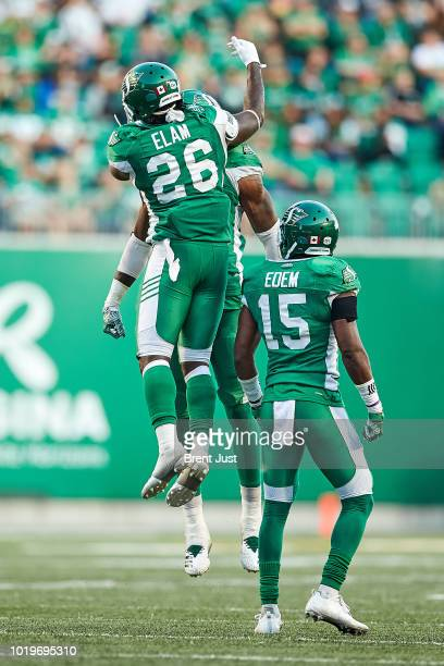 Matt Elam Mike Edem and Willie Jefferson of the Saskatchewan Roughriders celebrate after a sack in the game between the Calgary Stampeders and...
