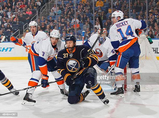 Matt Ellis of the Buffalo Sabres falls to his knee while battling for position with Travis Hamonic Thomas Hickey and goaltender Anders Nilsson of the...
