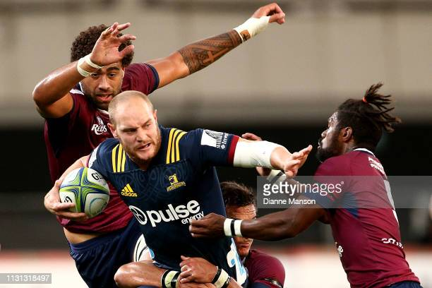 Matt Faddes of the Highlanders fends off Moses Sorovi of the Queensland Reds during the Round 2 Super Rugby match between the Otago Highlanders and...
