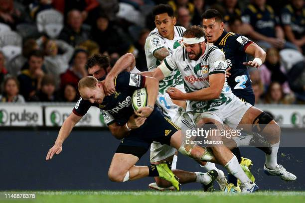 Matt Faddes of the Highlanders is tackled by Tyler Ardron of the Chiefs during the Round 12 Super Rugby match between the Highlanders and the Chiefs...