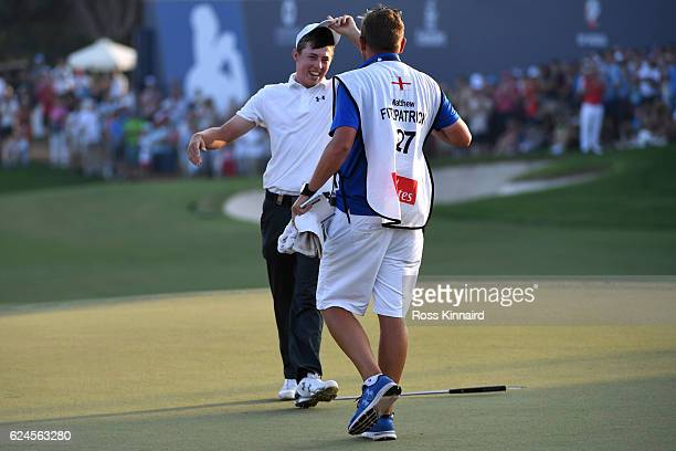 Matt Fitzpatrick of England celebrates holing the winning putt on the 18th green with his caddie Jamie Lane during day four of the DP World Tour...