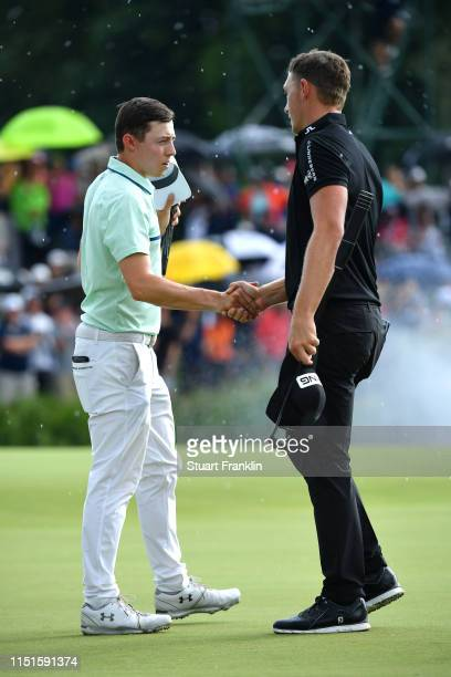 Matt Fitzpatrick of England shakes hands with Matt Wallace of England on the 18th green during day four of the BMW International Open at Golfclub...