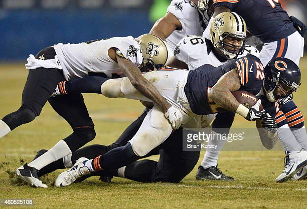 Matt Forte of the Chicago Bears is tackled by Keenan Lewis and Ben Grubbs of the New Orleans Saints during the second quarter at Soldier Field on...