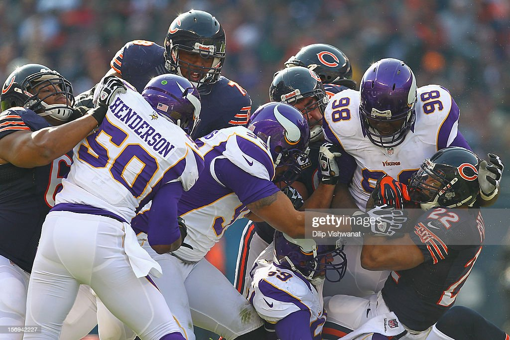 Matt Forte #22 of the Chicago Bears is tackled by Letroy Guion #98 and Kevin Williams #93 both of the Minnesota Vikings at Soldier Field on November 25, 2012 in Chicago, Illinois.