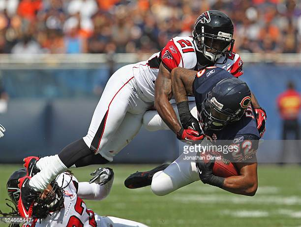 Matt Forte of the Chicago Bears is tripped up by Dunta Robinson and Chris Owens of the Atlanta Falcons at Soldier Field on September 11 2011 in...