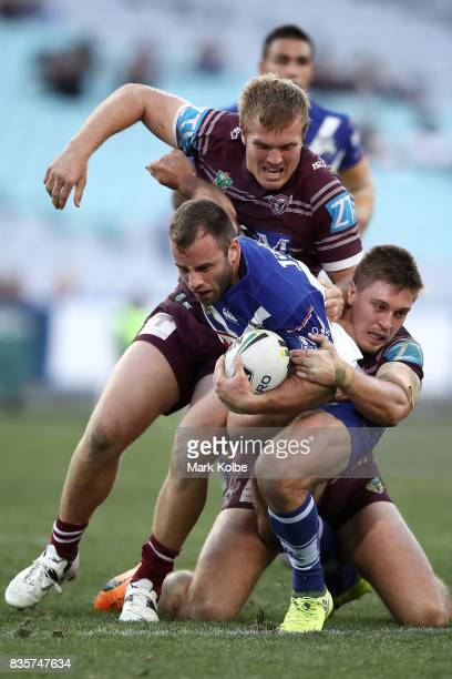 Matt Frawley of the Bulldogs is tackled during the round 24 NRL match between the Canterbury Bulldogs and the Manly Sea Eagles at ANZ Stadium on...