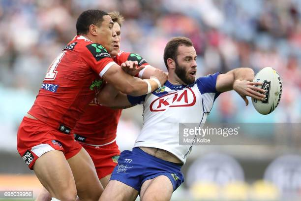 Matt Frawley of the Bulldogs passes as he is tackled during the round 14 NRL match between the Canterbury Bulldogs and the St George Illawarra...