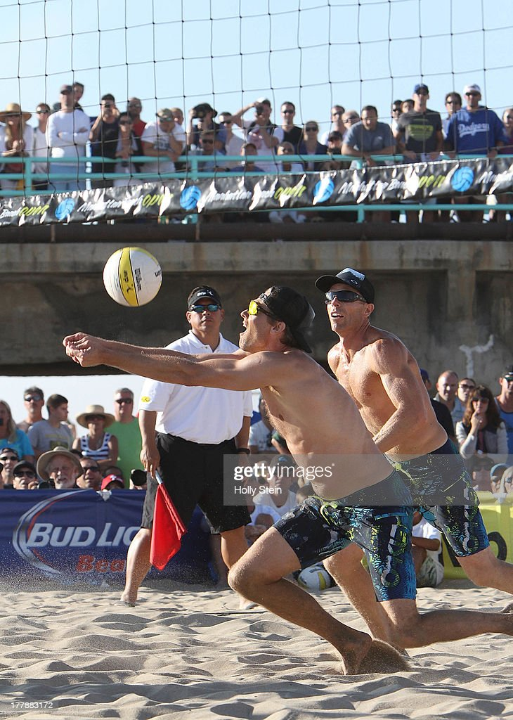 Matt Fuerbringer (L) digs the ball while partner Casey Jennings watches during their men's finals game at the AVP Manhattan Beach Open on August 25, 2013 in Manhattan Beach, California. Fuerbringer and Jennings defeated Sean Rosenthal and Phil Dalhausser 21-18, 21-23, 15-12.