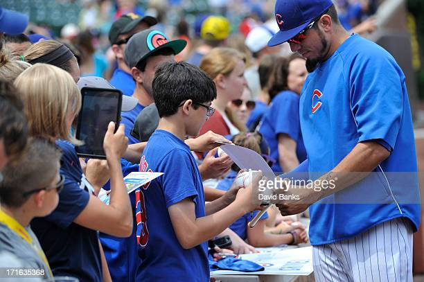 Matt Garza of the Chicago Cubs signs autographs before the game against the Houston Astros on June 22 2013 at Wrigley Field in Chicago Illinois