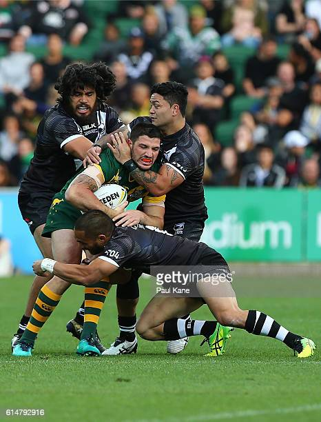 Matt Gillett of Australia gets tackled by Tohu Harris Thomas Leuluai and Issac Luke of New Zealand during the International Rugby League Test match...