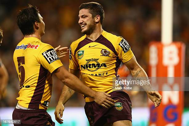 Matt Gillett of the Broncos is congratulated by his team mates after scoring a try during the round seven NRL match between the Wests Tigers and the...