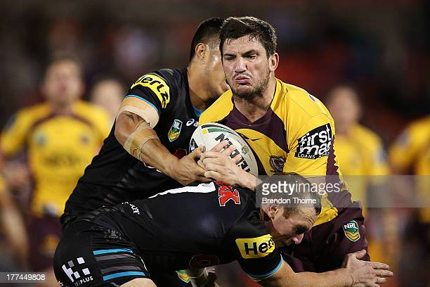 Matt Gillett of the Broncos is tackled by the Panthers defence during the round 24 NRL match between the Penrith Panthers and the Brisbane Broncos at...