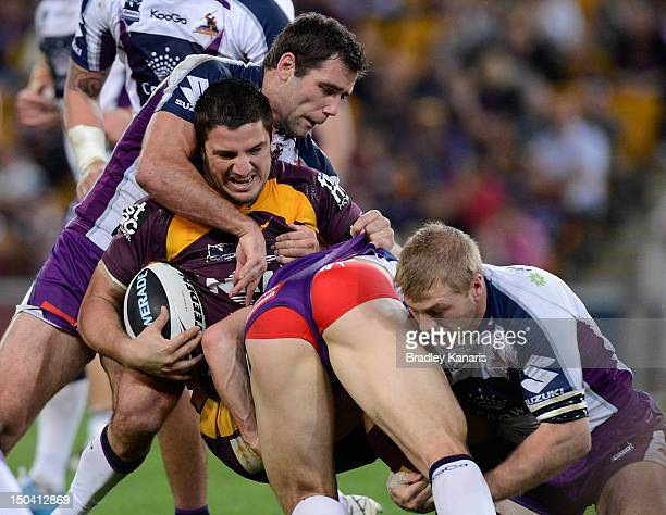 Matt Gillett of the Broncos is tackled during the round 24 NRL match between the Brisbane Broncos and the Melbourne Storm at Suncorp Stadium on...
