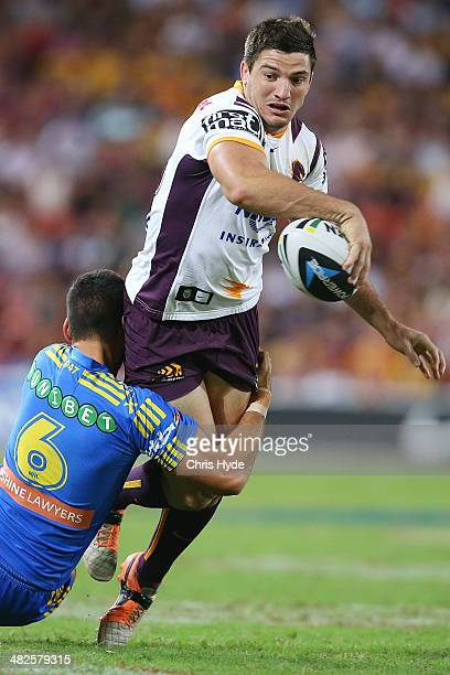 Matt Gillett of the Broncos passes while being tackled by Corey Norman of the Eels during the round five NRL match between the Brisbane Broncos and...