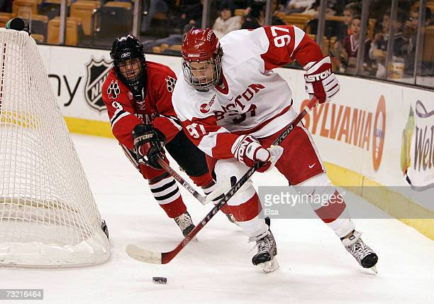 Matt Gilroy of the Boston University Terriers takes the puck as Jacques Perreault of the Northeastern Huskies defends during the Beanpot Tournament...