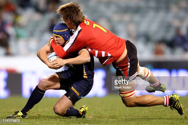 Matt Giteau of the Brumbies is tackled by Michael Rhodes of the Lions during the round 13 Super Rugby match between the Brumbies and the Lions at...