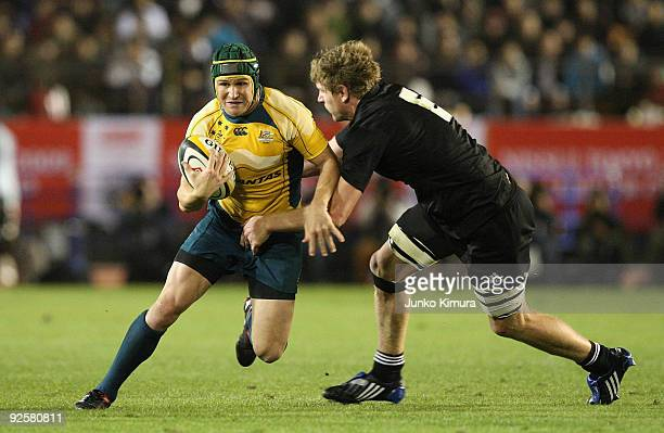 Matt Giteau of the Wallabies is challenged by Adam Thomson of the All Blacks during the 2009 Bledisloe Cup match between the New Zealand All Blacks...