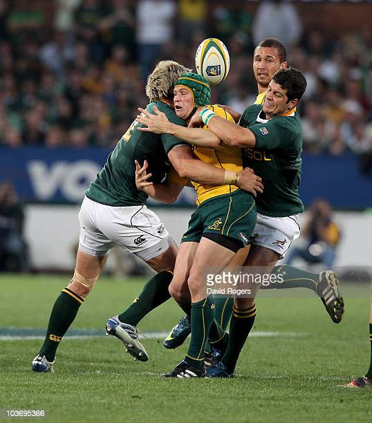 Matt Giteau of the Wallabies is tackled by Jean de Villiers and Morne Steyn during the 2010 TriNations match between the South African Springboks and...