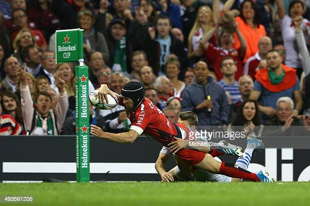 Matt Giteau of Toulon dives over to score the opening try despite the challenge from Richard Wigglesworth of Saracens during the Heineken Cup Final...
