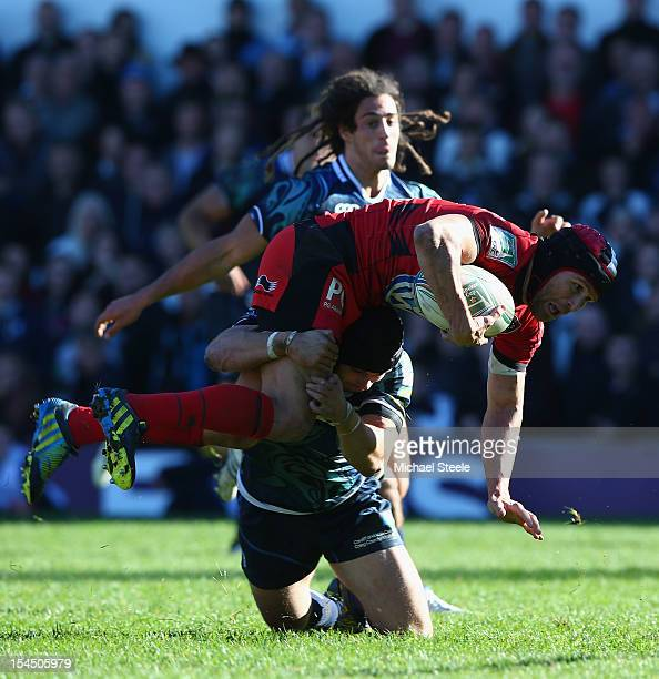 Matt Giteau of Toulon is upended in a tackle by Leigh Halfpenny of Cardiff Blues during the Heineken Cup Pool Six match between Cardiff Blues and...