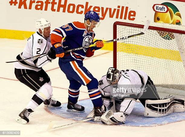 Matt Greene of the Los Angeles Kings checks Connor McDavid of the Edmonton Oilers into Kings goaltender Jack Campbell, who controls the puck during...