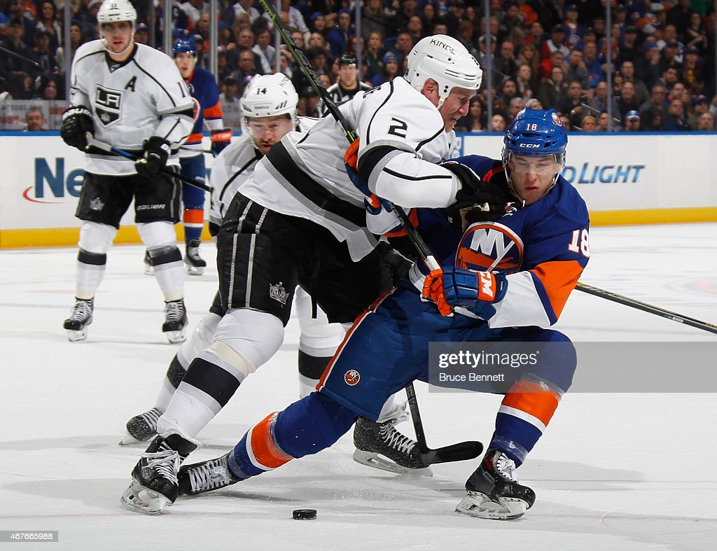 Matt Greene #2 of the Los Angeles Kings checks Ryan Strome #18 of the New York Islanders during the second period at the Nassau Veterans Memorial Coliseum on March 26, 2015 in Uniondale, New York.