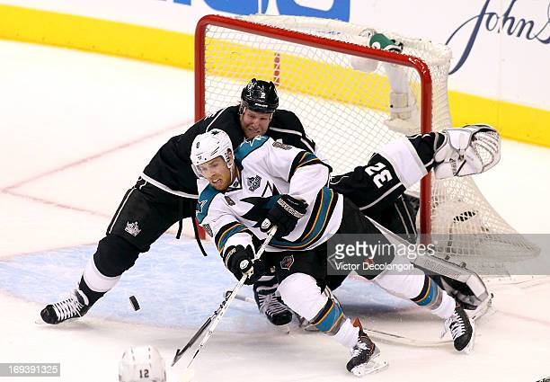 Matt Greene of the Los Angeles Kings defends the play of Joe Pavelski of the San Jose Sharks near the Kings crease area in the third period of Game...