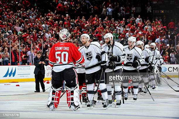 Matt Greene of the Los Angeles Kings shakes hands with goalie Corey Crawford of the Chicago Blackhawks after the Blackhawks won to become the 2013...