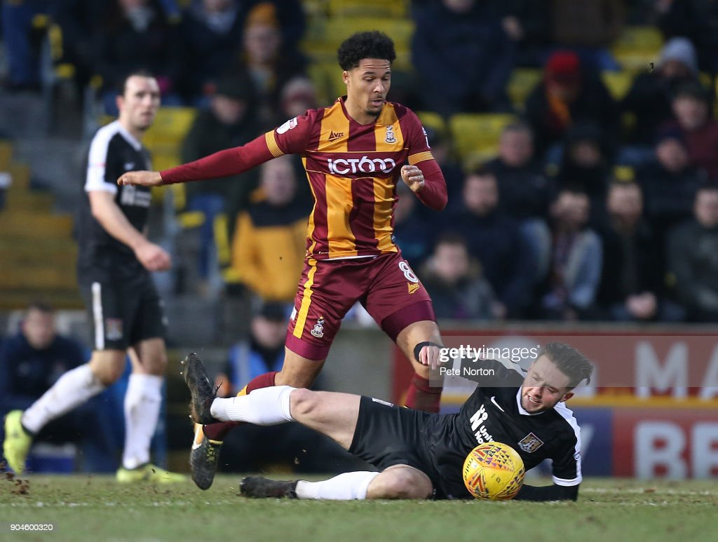 Matt Grimes of Northampton Town goes to ground under the challenge of Timothee Dieng of Bradford City during the Sky Bet League One match between Bradford City and Northampton Town at Northern Commercials Stadium, Valley Parade on January 13, 2018 in Bradford, England.