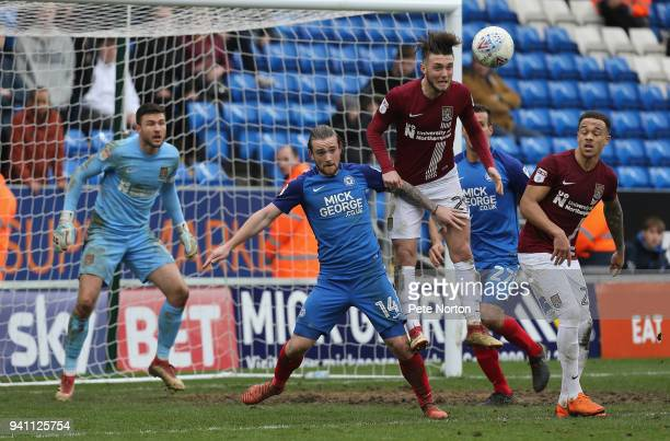 Matt Grimes of Northampton Town heads the ball away from Jack Marriott of Peterborough United during the Sky Bet League One match between...