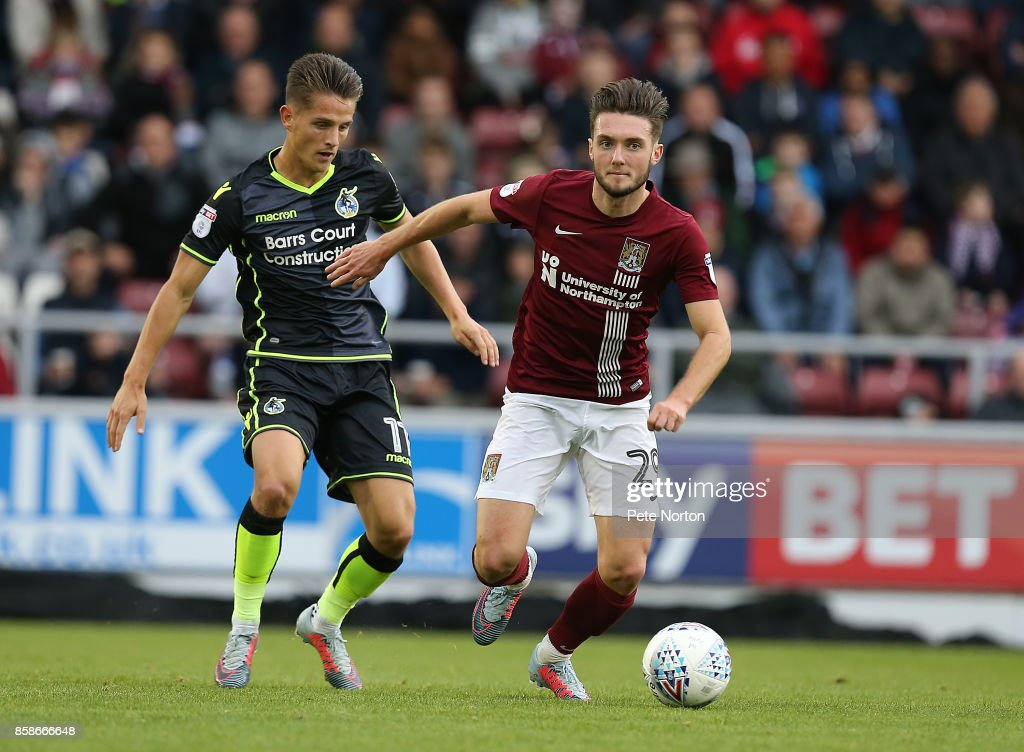 Matt Grimes of Northampton Town looks to plat the ball watched by Tom Nichols of Bristol Rovers during the Sky Bet League One match between Northampton Town and Bristol Rovers at Sixfields on October 7, 2017 in Northampton, England.