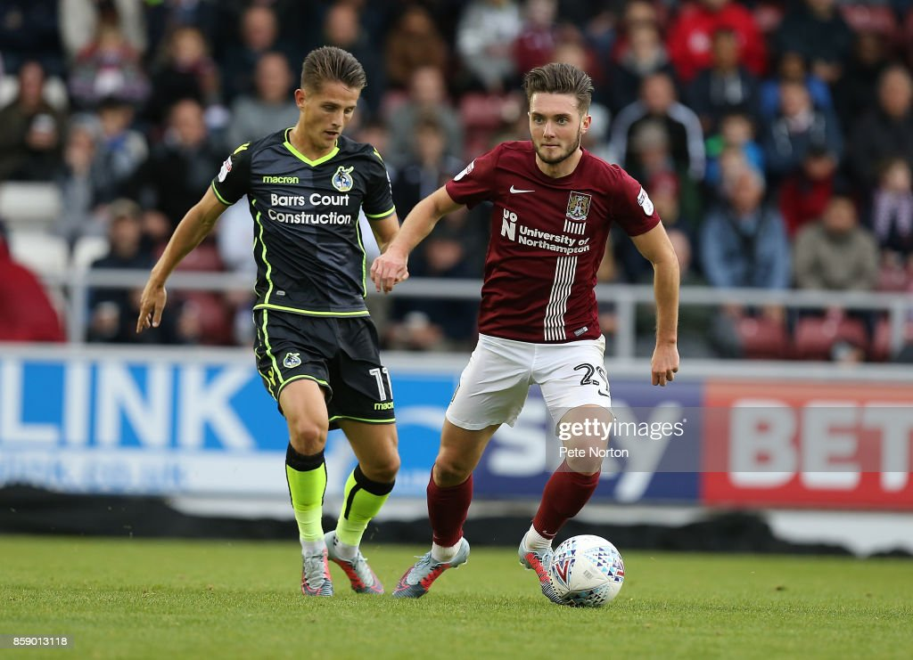 Matt Grimes of Northampton Town looks to play the ball watched by Tom Nichols of Bristol Rovers during the Sky Bet League One match between Northampton Town and Bristol Rovers at Sixfields on October 7, 2017 in Northampton, England.