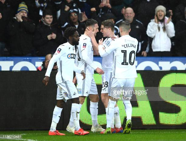 Matt Grimes of Swansea City celebrates with teammates after scoring his team's first goal during the FA Cup Quarter Final match between Swansea City...