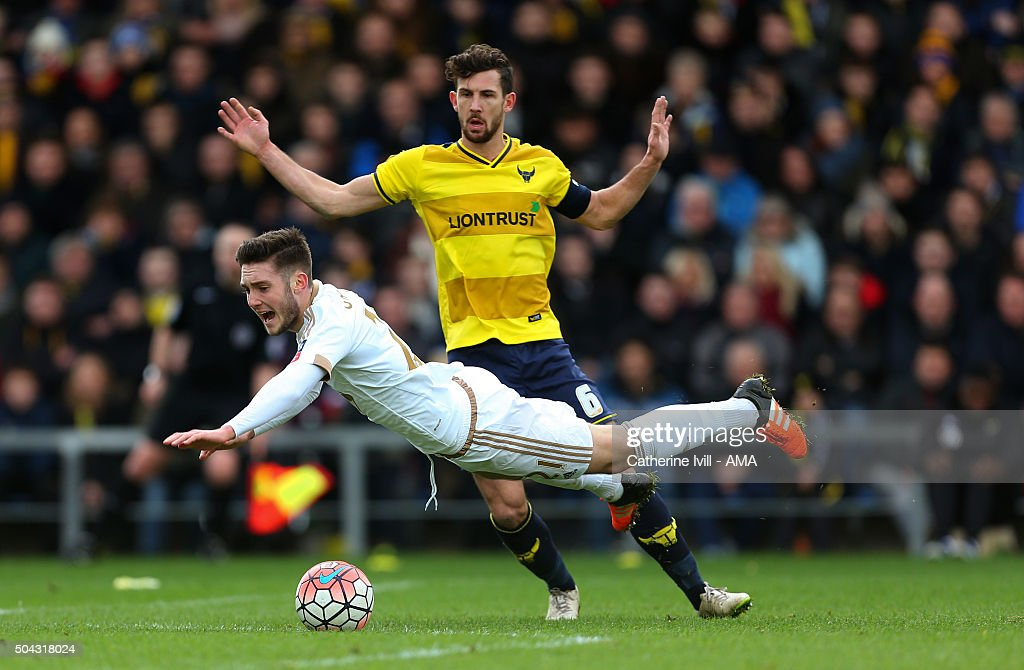 Matt Grimes of Swansea City flies over Jake Wright of Oxford United and receives a yellow card for diving during The Emirates FA Cup match between Oxford United and Swansea City at Kassam Stadium on January 10, 2016 in Oxford, England.