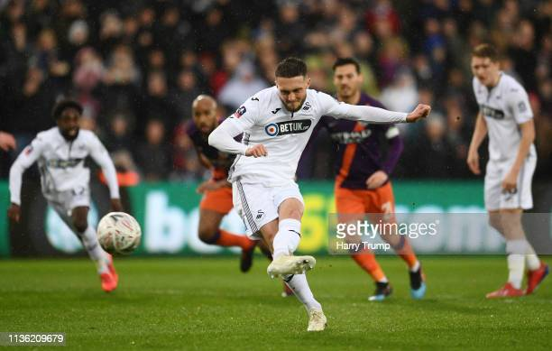 Matt Grimes of Swansea City scores his team's first goal from the penalty spot during the FA Cup Quarter Final match between Swansea City and...