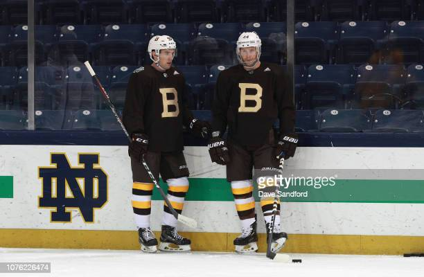 Matt Grzelcyk and Steven Kampfer of the Boston Bruins look on from the side boards during practice at Notre Dame Compton Family Ice Arena on December...